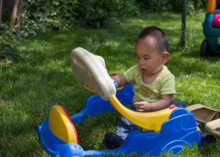 A little Chinese boy is playing toy on grassland in back yard.